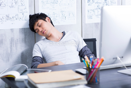 Young man taking a nap in the officeの写真素材 [FYI02213411]
