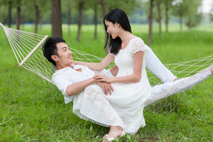 Sweet young couple in a hammock outdoorsの写真素材 [FYI02213422]