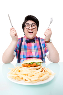 Overweight young man eating fast foodの写真素材 [FYI02213450]