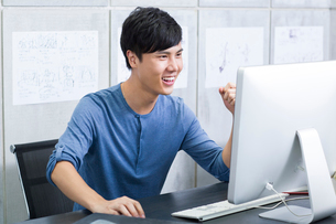 Young man celebrating in officeの写真素材 [FYI02213454]
