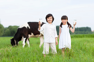 Happy children holding glasses of milk with cattle grazing iの写真素材 [FYI02213457]