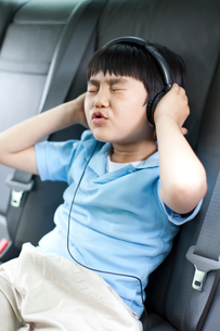 Cute boy listening to music and singing in carの写真素材 [FYI02213471]