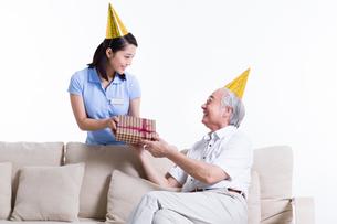 Female nursing worker giving birthday present to senior manの写真素材 [FYI02213491]