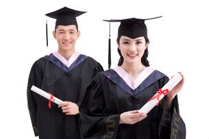 Happy college graduates in graduation gownsの写真素材 [FYI02213517]