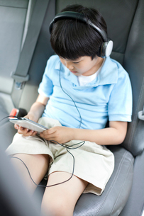 Cute boy listening to music with smart phone in carの写真素材 [FYI02213579]