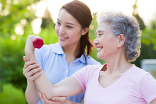 Senior woman exercising with dumbbell in nursing homeの写真素材 [FYI02213581]