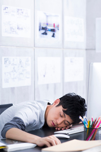 Young man taking a nap in the officeの写真素材 [FYI02213593]