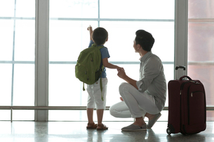 Father and son looking at view at the airportの写真素材 [FYI02213627]