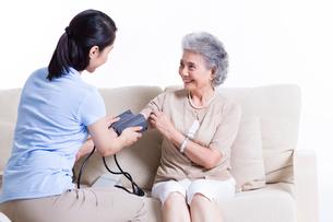 Nursing assistant taking senior woman's blood pressureの写真素材 [FYI02213657]
