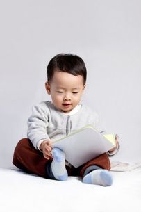 Cute little boy reading a bookの写真素材 [FYI02213665]