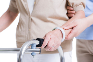 Nursing assistant helping senior woman with walking frameの写真素材 [FYI02213716]
