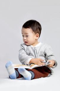 Cute little boy reading a bookの写真素材 [FYI02213760]