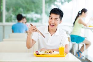 Happy young man dining in restaurantの写真素材 [FYI02213763]