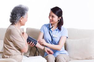Nursing assistant taking senior woman's blood pressureの写真素材 [FYI02213767]
