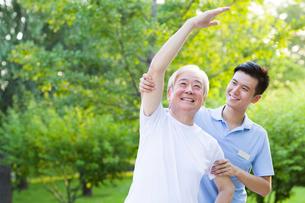 Senior man exercising with nursing assistant's helpの写真素材 [FYI02213769]