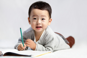 Cute little boy lying on front and writingの写真素材 [FYI02213778]