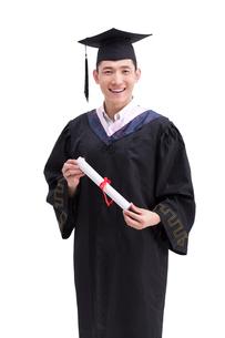Happy college graduate in graduation gownの写真素材 [FYI02213785]