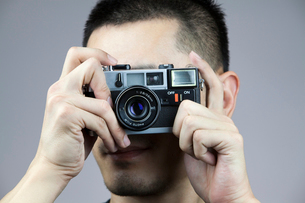 Young man taking photos with old-fashioned cameraの写真素材 [FYI02213786]