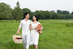 Happy young couple going for a picnic on the grassの写真素材 [FYI02213794]