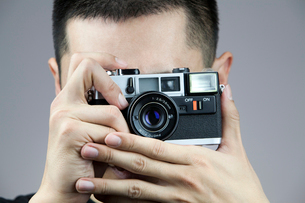 Young man taking photos with old-fashioned cameraの写真素材 [FYI02213800]