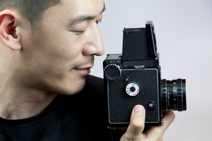 Young man taking photos with old-fashioned cameraの写真素材 [FYI02213811]