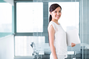Young businesswoman with laptop in the officeの写真素材 [FYI02213818]