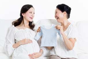 Mother and daughter preparing baby clothingの写真素材 [FYI02213837]