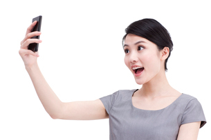 Young businesswoman photographs with mobile phoneの写真素材 [FYI02213843]