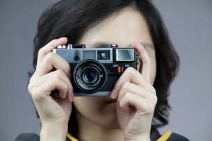 Young woman taking photos with old-fashioned cameraの写真素材 [FYI02213859]