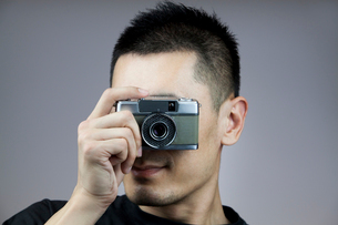 Young man taking photos with old-fashioned cameraの写真素材 [FYI02213897]