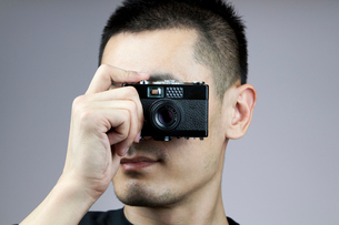 Young man taking photos with old-fashioned cameraの写真素材 [FYI02213935]