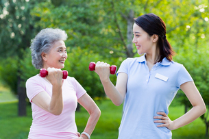 Senior woman exercising with dumbbell in nursing homeの写真素材 [FYI02213974]