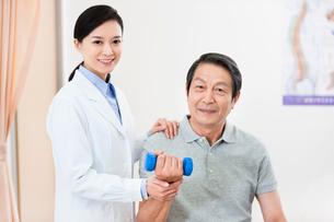 Senior patient exercising with dumbbell under doctor's helpの写真素材 [FYI02213989]