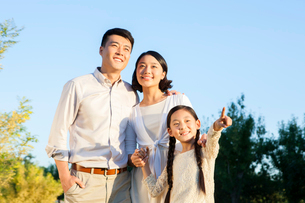 Cheerful young family looking at view in a parkの写真素材 [FYI02213999]