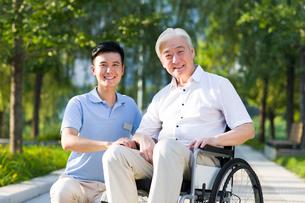 Wheelchair bound man with nursing assistantの写真素材 [FYI02214002]