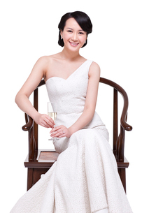 Elegant young woman sitting on Chinese Ming-style wooden armchair with champagne fluteの写真素材 [FYI02214023]