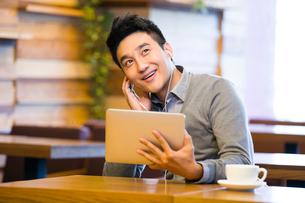 Young man enjoying music in digital tablet in coffee shopの写真素材 [FYI02214034]