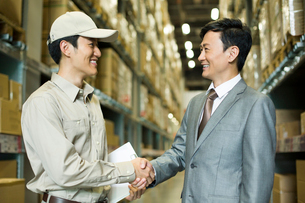 Young logistics staff shaking hands with businessmanの写真素材 [FYI02214096]