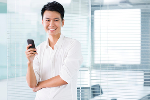 Young man with mobile phone in officeの写真素材 [FYI02214122]