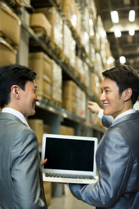 Business partners with laptop in logistic warehouseの写真素材 [FYI02214132]