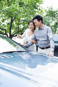 Happy couple buying a new carの写真素材 [FYI02214133]