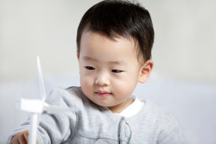 Cute little boy playing paper windmillの写真素材 [FYI02214146]