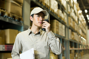 Young logistics staff using walkie-talkie in warehouseの写真素材 [FYI02214174]