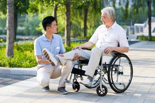 Wheelchair bound man with nursing assistantの写真素材 [FYI02214187]