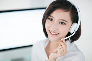Cheerful businesswoman with headset in officeの写真素材 [FYI02214192]