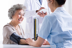 Nurse taking senior woman's blood pressureの写真素材 [FYI02214213]