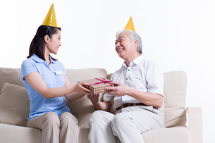 Female nursing worker giving birthday present to senior manの写真素材 [FYI02214239]