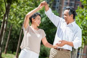 Cheerful mature couple dancing outdoorsの写真素材 [FYI02214257]