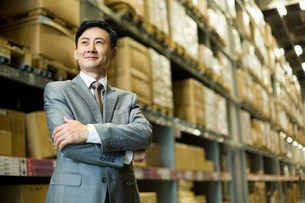 Confident businessman arms crossed in warehouseの写真素材 [FYI02214281]