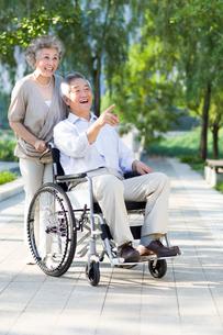 Senior woman with wheelchair bound husbandの写真素材 [FYI02214310]